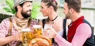 Les gens avec de la bière et le bretzel dans l'auberge de Bavaian Image stock