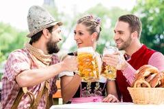 Les gens avec de la bière et le bretzel dans l'auberge de Bavaian Photo stock