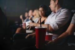 Les gens avec des boissons non alcoolisées dans le film de observation Photo stock