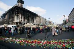 Les gens avec des fleurs sont venus bâtiment brûlé par passé Photos stock