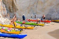 Les gens avec des kayaks sur Gerontas échouent, Melos, Grèce Photos stock