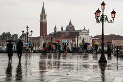 Les gens avec des parapluies sur le bord de mer à Venise Photographie stock libre de droits