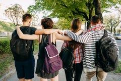 Les gens avec des sacs à dos étreignant la marche dans la ville Images stock