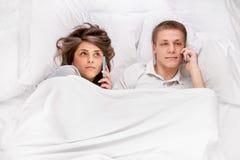 Les gens avec des smartphones dans le lit Image stock