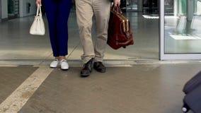 Les gens avec des valises quittant l'aéroport, arrivée après voyage d'affaires, vacances banque de vidéos