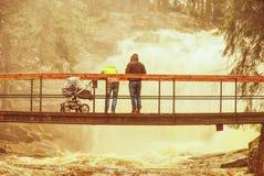 Les gens avec le b?b? sur le pont ?tir? au-dessus de la rivi?re de montagne d'inondation photo stock