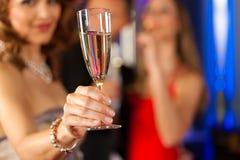 Les gens avec le champagne dans un bar Image stock