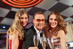 Les gens avec le champagne dans un bar Photo stock