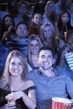 Les gens avec le film de observation de soude et de maïs éclaté dans le théâtre Photographie stock libre de droits