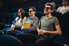 Les gens avec le film de observation de maïs éclaté dans le cinéma Image libre de droits