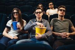 Les gens avec le film de observation de maïs éclaté dans le cinéma Photo libre de droits