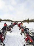 Les gens avec le scooter de neige en tournée Photo stock
