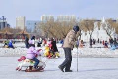 Les gens ayant l'amusement avec sledging sur la glace dans le parc de Nanhu, Tchang-tchoun, Chine Photographie stock libre de droits