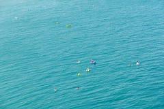 Les gens ayant l'amusement dans des panneaux de petits bateaux et de palette de ressac sur la mer Méditerranée Photos stock
