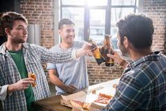 Les gens ayant l'amusement tout en buvant de la bière et mangeant de la pizza à la maison Photographie stock