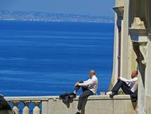 Les gens ayant la pause de midi Deux hommes regardant l'horizon fixement de mer Images stock