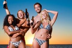 Les gens ayant la réception à la plage avec des boissons Photos stock