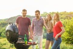 Les gens ayant le barbecue dans la région sauvage Saison de camping Images libres de droits