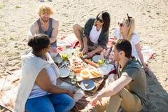 Les gens ayant le pique-nique sur la plage Image libre de droits