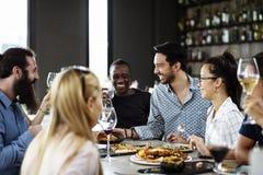 Les gens ayant le repas ensemble dans le restaurant image stock