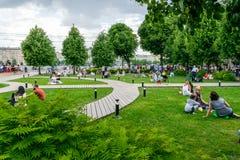 Les gens ayant le repos sur l'herbe dans le parc de Gorki Image libre de droits