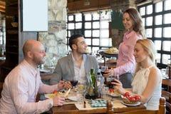 Les gens ayant le restaurant rural de dîner Photographie stock libre de droits