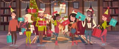 Les gens célèbrent des hommes de Joyeux Noël et de bonne année et des vacances Eve Party de Santa Hats Hold Gift Boxes de vêtemen Photo stock