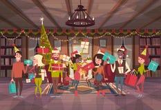 Les gens célèbrent des hommes de Joyeux Noël et de bonne année et des vacances Eve Party de Santa Hats Hold Gift Boxes de vêtemen Photographie stock libre de droits