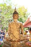 Les gens collant la feuille de feuille d'or sur la statue arrière de Bouddha pour le respect images stock
