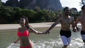 Les gens courant dans l'eau sur la plage dans les montagnes, l'homme de sourire heureux et les touristes de groupe de femme banque de vidéos