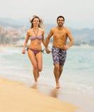 Les gens courant dans les vêtements de bain sur la mer ondulent Photographie stock libre de droits