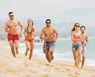 Les gens courant ensemble à la plage d'océan Images stock