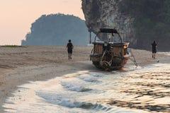 Les gens courant le long du littoral de mer dehors le soir photographie stock libre de droits