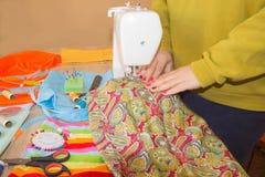 Les gens, couture, cousant et travaillant le concept - la femme de tailleur avec le fil dans le tissu piquant d'aiguille rassembl Images stock
