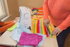 Les gens, couture, cousant et travaillant le concept - la femme de tailleur avec le fil dans le tissu piquant d'aiguille rassembl Image stock