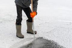 Les gens dégagent un trou dans l'étang de glace pour nager Natation d'hiver RP image stock
