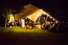 Les gens détendant dans une tente la nuit Photographie stock