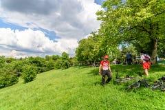Les gens détendant et ayant le pique-nique en parc public des jeunesse Image stock