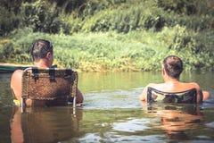 Les gens détendant pendant leurs vacances de camping de loisirs sur la rivière et regardant sur le beau paysage Photographie stock