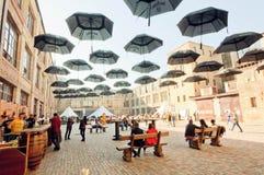 Les gens détendant sous des parapluies à la barre extérieure de la ville Images libres de droits