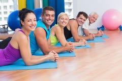 Les gens détendant sur des tapis d'exercice dans le studio de forme physique Photos libres de droits