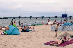 Les gens détendant sur la plage se trouvant sur le sable et sur leurs serviettes/couvertures, prenant un bain de soleil et appréc images stock