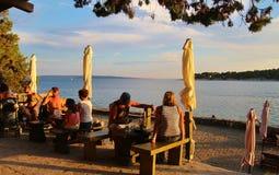 Les gens détendent sur une terrasse de café, sur la promenade de bord de la mer de la ville de Rab Croatie photos libres de droits