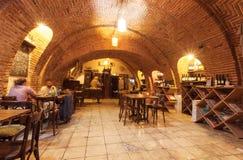 Les gens dînant à l'intérieur de vieille cave de voûte de brique avec la nourriture et le vin, vieux restaurant de mode de Tbilis photographie stock libre de droits