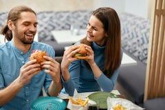 Les gens dînant, mangeant des hamburgers au café Image libre de droits