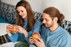 Les gens dînant, mangeant des hamburgers au café Photos stock