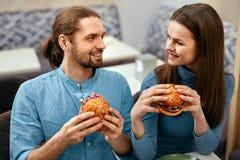 Les gens dînant, mangeant des hamburgers au café Images stock