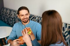 Les gens dînant, mangeant des hamburgers au café Images libres de droits
