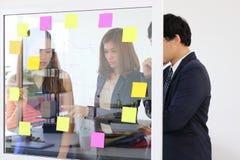Les gens d'affaires asiatiques emploient des notes de post-it sur le mur de verre pour partager l'idée au lieu de réunion travail image libre de droits