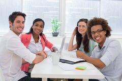Les gens d'affaires ayant une réunion sourient ensemble à l'appareil-photo Photographie stock